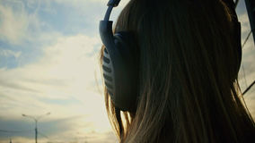Cute young girl in headphones in park at dusk. close up. Cute young girl with headphones in park at dusk. close up Royalty Free Stock Photo