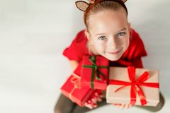 Cute young girl holding christmas presents, smiling and looking at camera. Happy kid at christmas time sitting on the floor. stock photo