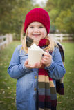 Cute Young Girl Holding Cocoa Mug with Marsh Mallows Outside. Cute Smiling Young Girl Wearing Hat and Scarf Holding Cocoa Mug with Marsh Mallows Outside Stock Photography