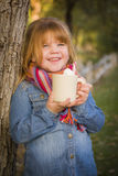 Cute Young Girl Holding Cocoa Mug with Marsh Mallows Outside. Cute Smiling Young Girl Wearing Hat and Scarf Holding Cocoa Mug with Marsh Mallows Outside Royalty Free Stock Photography