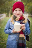 Cute Young Girl Holding Cocoa Mug with Marsh Mallows Outside. Cute Smiling Young Girl Wearing Hat and Scarf Holding Cocoa Mug with Marsh Mallows Outside Royalty Free Stock Image