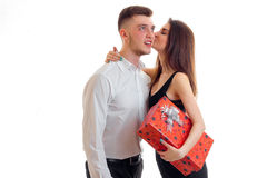 Cute young girl holding a gift and kisses the handsome guy smiling royalty free stock image