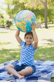 Cute young girl holding globe at park Royalty Free Stock Photography