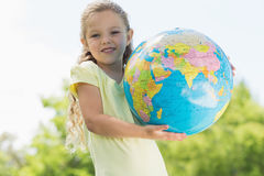 Cute young girl holding globe at park Stock Photos