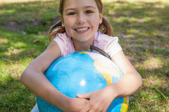 Cute young girl holding globe at park Stock Images
