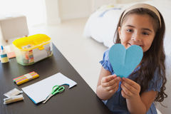 Cute young girl holding heartshape paper at table Royalty Free Stock Photo