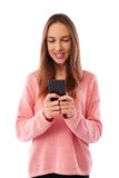 Cute young girl holding mobile phone while standing against whit Royalty Free Stock Photos