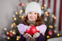 Cute young girl holding out a Christmas bauble Royalty Free Stock Photography