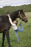 Cute young girl hugging beautiful horse's neck and looking at the camera. Lifestyle portrait Royalty Free Stock Photo