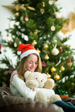 Cute young girl hugs teddy bear in christmas eve Royalty Free Stock Photo