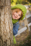 Cute Young Girl In Green Scarf And Hat Plays Peekaboo Royalty Free Stock Image