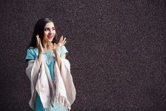 Cute young girl joyfully poses on brown wall background. royalty free stock photo