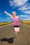Cute young girl jumping under a blue sky Royalty Free Stock Photo