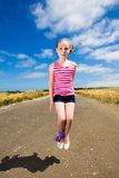 Cute young girl jumping under a blue sky Royalty Free Stock Photography