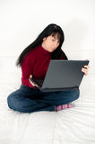 Cute young girl with laptop in bedroom Royalty Free Stock Photography