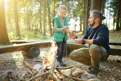 Cute young girl learning to start a bonfire. Father teaching her daughter to make a fire. Child having fun at camp fire. Camping stock image