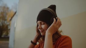 Cute young girl listening music in headphones and dancing, urban style, stylish hipster teen in black hat listen music stock footage