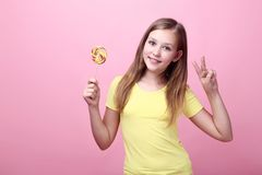 Young girl with lollipop. Cute young girl with lollipop on pink background royalty free stock images