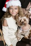 Cute young girl with long blond hair and a Santa Claus hat holding a puppy breed yorkshire terrier which also has a cap of Santa C Royalty Free Stock Photo