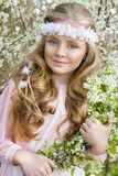 Cute young girl with long blond hair standing in a meadow in wreath of flowers, holding a bouquet of spring flowers Royalty Free Stock Photography