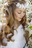 Cute young girl with long blond hair standing in a meadow in wreath of flowers, holding a bouquet of spring flowers Royalty Free Stock Photo