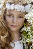 Cute young girl with long blond hair standing in a meadow in wreath of flowers, holding a bouquet of spring flowers Stock Images
