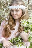 Cute young girl with long blond hair standing in a meadow in wreath of flowers, holding a bouquet of spring flowers Royalty Free Stock Image