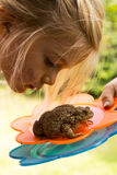 A cute young girl looking close at toad (frog) Royalty Free Stock Photography
