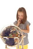 Cute young girl looking at world globe with finger Royalty Free Stock Photos