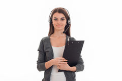 Cute young girl looks right standing with headphones and holding a Tablet for securities Stock Images