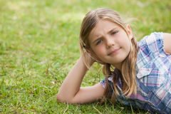 Cute young girl lying on grass at park Stock Photos