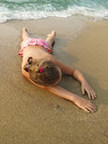 Cute little girl lying on a sandy beach summertime Stock Images