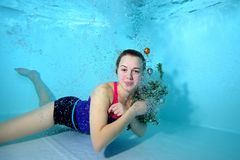 Cute young girl lying underwater at the bottom of the pool in air bubbles, looking at camera and smiling. Portrait. Horizontal orientation. A view from under Royalty Free Stock Photography
