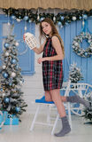 Cute young girl near the christmas tree with a gift in her hands Stock Images