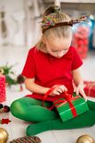 Cute young girl opening christmas present while sitting on living room floor. Candid family christmas time background. Cute young girl opening christmas present stock photo