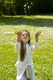 Cute young girl in the park. Beautiful young girl in park throwing flowers in the air Stock Photography