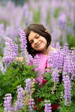 Cute Young Girl in Patch of Purple Wild Flowers. A cute young girl with dark hair plays in a patch of wild purple lupine flowers. Shallow depth of field Royalty Free Stock Photos