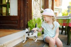 Cute young girl petting a friendly Greek cat on warm and sunny summer day during family vacations in Kalavryta, Greece. Cute young girl petting a friendly Greek royalty free stock image
