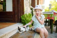 Cute young girl petting a friendly Greek cat on warm and sunny summer day during family vacations in Kalavryta, Greece. Cute young girl petting a friendly Greek stock photos