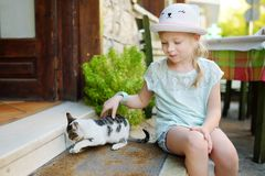 Cute young girl petting a friendly Greek cat on warm and sunny summer day during family vacations in Kalavryta, Greece. Cute young girl petting a friendly Greek royalty free stock photography