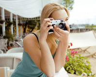 Cute young girl with photo camera shooting Stock Images