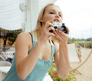 Cute young girl with photo camera shooting Royalty Free Stock Image