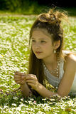 Cute young girl picking flowers. Beautiful young girl in park picking daisies Stock Images