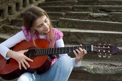 Cute Young Girl Playing a Guitar Against Old Stone Staircase Stock Images