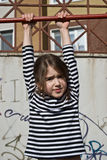 Cute young girl playing on the monkey bars. Funny eight-year girl hanging on the monkey bar Royalty Free Stock Photo