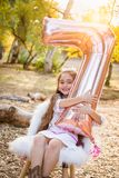 Cute Young Girl Playing With Number Seven Mylar Balloon Outdoors. Cute Young Girl Playing With a Number Seven Mylar Balloon Outdoors stock photos