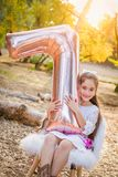 Sweet Young Girl With Number Seven Mylar Balloon Outdoors royalty free stock photos