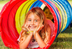 Cute Young Girl Playing. Outside in Colorful Tunnel Royalty Free Stock Image