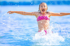 Cute young girl playing in the sea. Happy pre-teen girl enjoys summer water and holidays in holiday destinations.  Royalty Free Stock Image