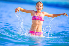 Cute young girl playing in the sea.  Happy pre-teen girl enjoys summer water and holidays in holiday destinations.  Stock Photography